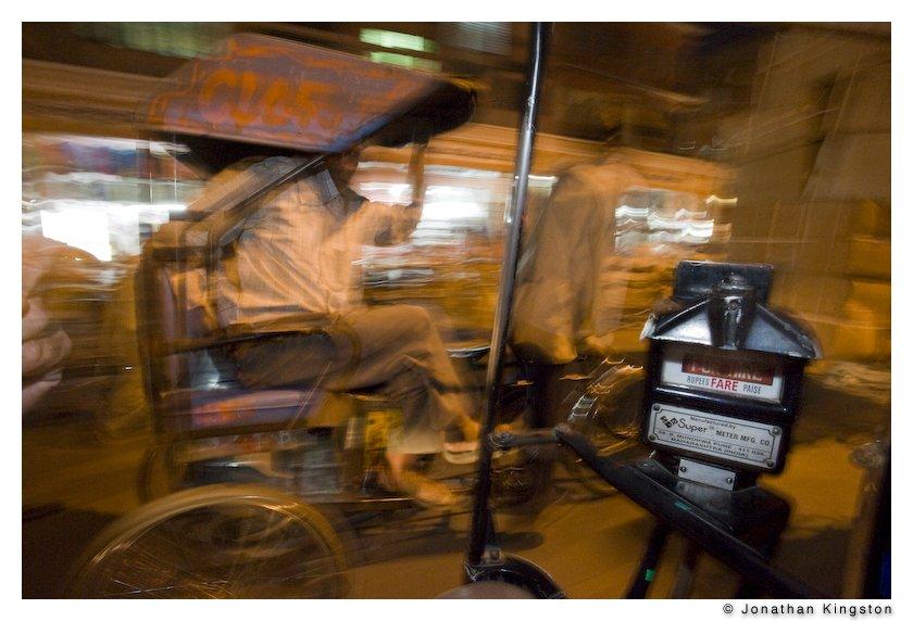 A bicycle rickshaw passes a petrol rickshaw at night in Jaipur, India
