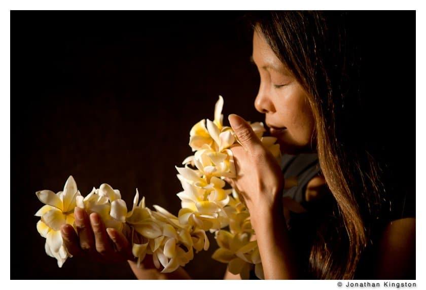 A hula dancer smells a lei of plumeria flowers on Molokai, Hawaii.