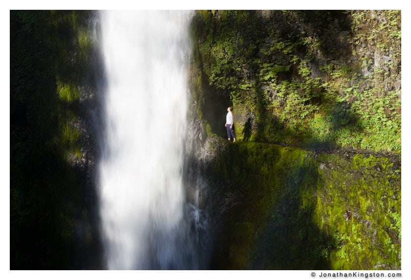 A woman looks in wonder at the beautiful Tunnel Falls on Eagle Creek trail in the Columbia River Gorge, Oregon, USA.